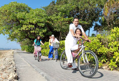 La guida asiatica felice della famiglia bikes nella bella mattina al Immagine Stock