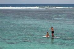La guida del giovane e della ragazza imbarca con un remo Eremo della laguna, la Riunione Fotografie Stock Libere da Diritti