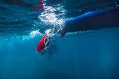 La guida del surfista sopra sta sul bordo di pagaia Colpo subacqueo con la pagaia e bordo in oceano fotografia stock