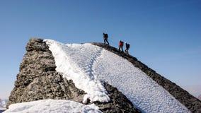 La guida della montagna raggiunge la sommità in alpi svizzere con due clienti Fotografie Stock