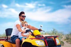 La guida felice della famiglia, del padre e del figlio sul atv quad la bici alla spiaggia sabbiosa immagine stock