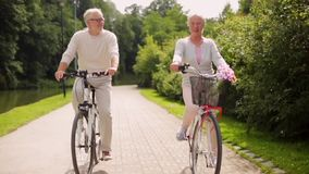 La guida senior felice delle coppie va in bicicletta al parco dell'estate video d archivio