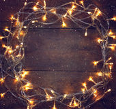 La guirlande chaude d'or de Noël coloré s'allume sur le fond rustique en bois Image filtrée Photos libres de droits