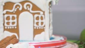 La guirlande colorée clignote sur un fond brouillé avec la maison de pain d'épice banque de vidéos