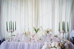 La guirlande de fleur des roses en forme de pin pend de la table Décoration de mariage, floristry Candélabres avec les bougies ve photos libres de droits
