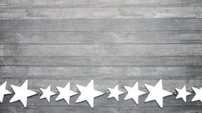 La guirlande de l'étoile argentée sur le vieux fond en bois photographie stock libre de droits