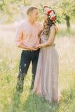 La guirlande de port de fleur de jeune belle fille avec son ami tenant des mains font du jardinage au printemps Image stock