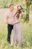 La guirlande de port de fleur de jeune belle fille avec son ami tenant des mains font du jardinage au printemps Photographie stock