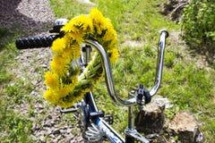 La guirlande du ressort jaune fleurit - des pissenlits sur la poignée de bicyclette Photographie stock