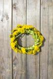 La guirlande du ressort jaune fleurit - des pissenlits sur un fond en bois, été romantique de ressort Photographie stock libre de droits