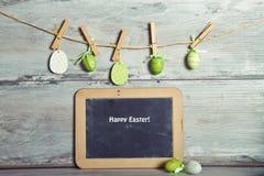 La guirnalda adornó los huevos y el mensaje de saludos Foto de archivo libre de regalías