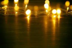 La guirnalda caliente del oro de la Navidad se enciende en fondo de madera trasero Imágenes de archivo libres de regalías