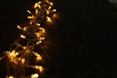 La guirnalda caliente del oro de la Navidad se enciende en fondo de madera trasero Foto de archivo libre de regalías