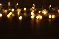 La guirnalda caliente del oro de la Navidad se enciende en fondo de madera trasero Fotos de archivo libres de regalías