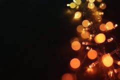 La guirnalda caliente del oro de la Navidad se enciende en fondo de madera trasero capa del brillo Fotos de archivo libres de regalías