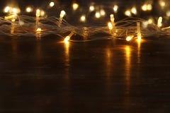 La guirnalda caliente del oro de la Navidad se enciende en fondo de madera trasero capa del brillo Imagen de archivo libre de regalías
