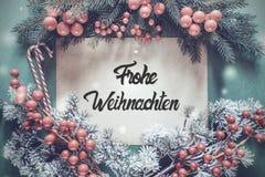 La guirnalda de Chrismtas, caligrafía Frohe Weihnachten significa Feliz Navidad fotografía de archivo