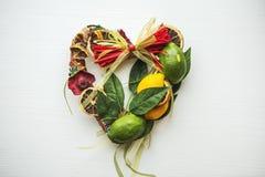 La guirnalda de mimbre con en forma de corazón, adornado con las hojas, limón, secó el limón Foto de archivo libre de regalías