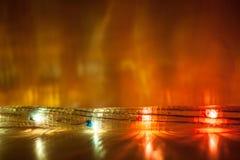 La guirnalda de la Navidad adentro está mintiendo en la tabla de madera y resplandores de luces en la pared fotografía de archivo