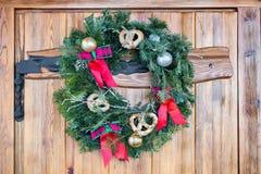 La guirnalda de la Navidad con los pretzeles, los arcos del rojo y el oro adorna la ejecución en la puerta de madera Fotografía de archivo
