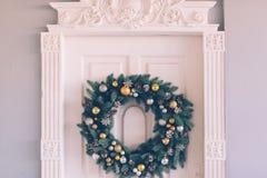 La guirnalda de la Navidad cuelga en la puerta Fotos de archivo libres de regalías