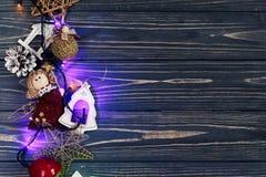 La guirnalda de la Navidad enciende los juguetes del ANG de la frontera en rústico negro elegante Foto de archivo