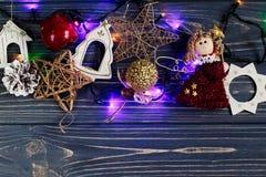 La guirnalda de la Navidad enciende los juguetes del ANG de la frontera en rústico negro elegante Fotografía de archivo libre de regalías