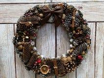 La guirnalda de la Navidad de los conos de abeto, nueces, bayas, broncea en un fondo beige del tablón fotos de archivo