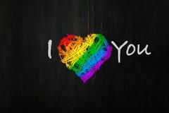 La guirnalda del corazón de las tarjetas del día de San Valentín del amor en orgullo del arco iris colorea el backg oscuro Imagen de archivo libre de regalías
