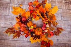 La guirnalda tejida adornó las hojas anaranjadas, verduras del otoño Imagen de archivo libre de regalías