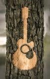 La guitare a découpé dans l'écorce d'un arbre Images libres de droits