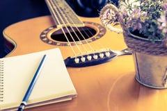 La guitare et le carnet pour l'équipement d'écriture d'amour fleurissent le seau Photos libres de droits