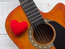 La guitare et le coeur rouge sur le fond en bois blanc de texture Lov Photos libres de droits