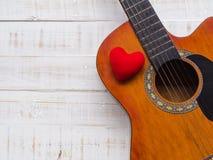 La guitare et le coeur rouge sur le fond en bois blanc de texture Lov Photo libre de droits