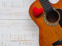 La guitare et le coeur rouge sur le fond en bois blanc de texture Lov Image stock
