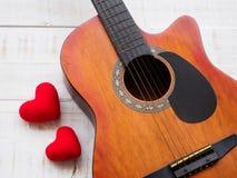 La guitare et le coeur rouge sur le fond en bois blanc de texture Lov Photos stock