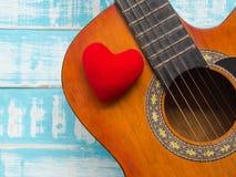 La guitare et le coeur rouge sur le fond en bois bleu de texture Amour Photographie stock