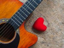 La guitare et le coeur rouge sur le fond en bois de texture Amour, Mus Photos stock