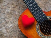 La guitare et le coeur rouge sur le fond en bois de texture Amour, Mus Images stock
