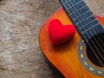 La guitare et le coeur rouge sur le fond en bois de texture Amour, Mus Photo stock