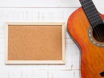 La guitare et le conseil sur le fond en bois blanc de texture Amour, M Photographie stock