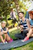 La guitare et les filles de jeu de type apprécie devant la tente au camp Photographie stock libre de droits