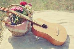 La guitare romantique de photo, panier avec du vin, bouquet fleurit sur le plaid Romance, amour, date, jour de valentines Photo stock
