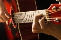 La guitarra acústica roja, fondo oscuro, sienta al músico que juega en el juego español, musical clásico de la escuela para los n Imagen de archivo libre de regalías