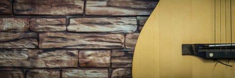 La guitarra acústica se coloca en un fondo de la pared de ladrillo fotos de archivo libres de regalías