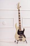 La guitarra baja se coloca cerca de la pared blanca Fotos de archivo libres de regalías