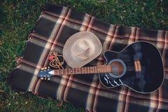 La guitarra, la cesta, los bocadillos, la tela escocesa y el jugo en una floración cultivan un huerto Fondo blando del vintage Ro fotografía de archivo libre de regalías