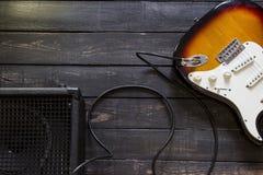 La guitarra eléctrica con el amplificador conectó por el cable en la parte posterior de madera Fotografía de archivo libre de regalías