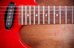 La guitarra eléctrica roja vieja que se coloca en un piso de madera Imagenes de archivo