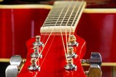 La guitarra roja acústica miente en la tabla en el fondo con una copia del espacio de la mano, tocando la guitarra acústica, prim Foto de archivo libre de regalías